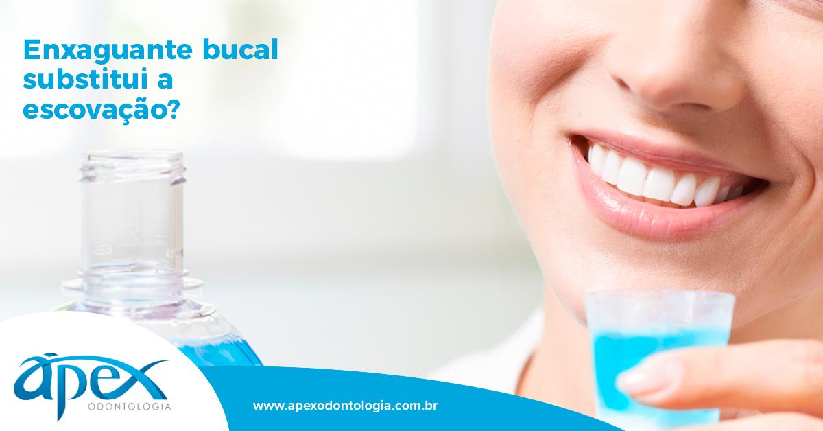 A imagem mostra o sorriso de uma mulher e a mão dela segurando um copinho com um líquido azul, que seria o enxaguante bucal.
